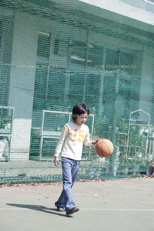 学校の校庭でバスケットボールをする男の子の素材 [FYI01019103]