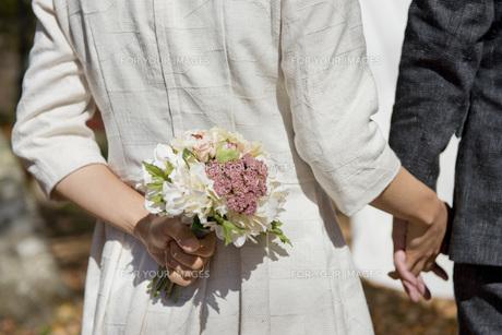 手をつないで歩くカップルとブーケの素材 [FYI01019526]
