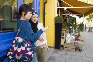 ロンドンの街角で携帯を見る20代女性2人の素材 [FYI01019693]