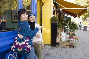 ロンドンの街角で携帯を見る20代女性2人の素材 [FYI01019726]
