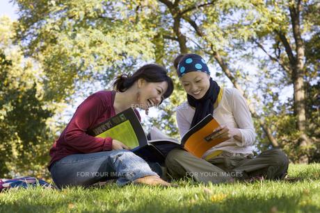 公園で本を読む20代女性2人の素材 [FYI01019793]