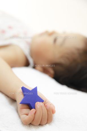 お星様を握って眠る女の子の素材 [FYI01019946]