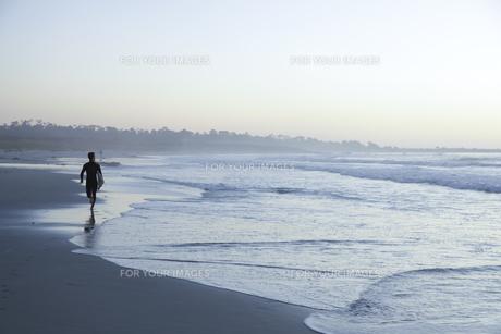 サーフボードを担いで海岸を走る人の素材 [FYI01020117]