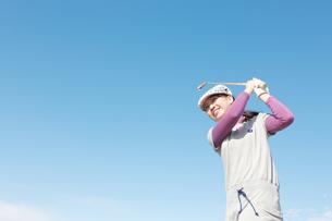 青空バックでゴルフの素振りをする若い女性の素材 [FYI01028091]
