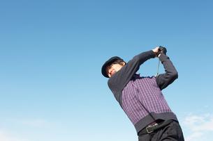 青空バックでゴルフの素振りをする若い男性の素材 [FYI01028101]