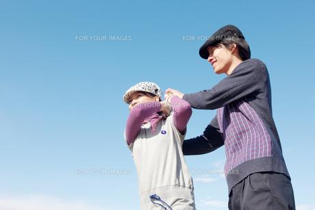 青空バックでゴルフの練習をする若いカップルの素材 [FYI01028103]