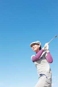 青空バックでゴルフの素振りをする若い女性の素材 [FYI01028106]