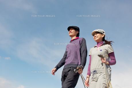 青空バックでゴルフクラブを持って歩く若いカップルの素材 [FYI01028158]