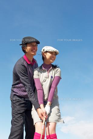 青空バックでゴルフの練習をする若いカップルの素材 [FYI01028159]