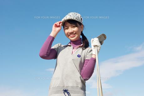 青空バックでゴルフクラブを持って微笑む若い女性の素材 [FYI01028166]