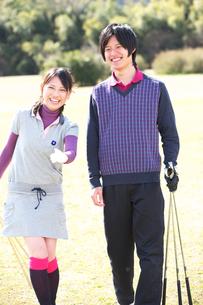 ゴルフクラブを持ってグリーンで指さす若いカップルの素材 [FYI01028198]