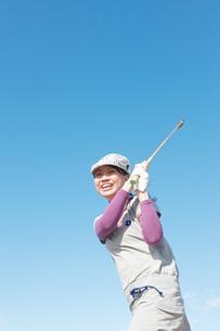 青空バックでゴルフの素振りをする若い女性の素材 [FYI01028199]