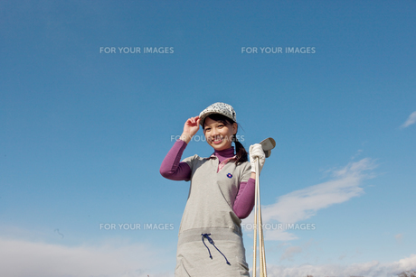 青空バックでゴルフクラブを持って微笑む若い女性の素材 [FYI01028230]