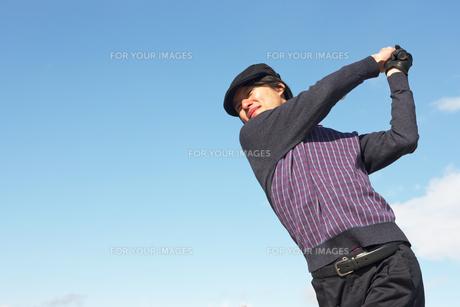 青空バックでゴルフの素振りをする若い男性の素材 [FYI01028272]