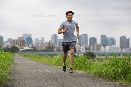 都会をバックにジョギングする20代男性の素材 [FYI01030309]