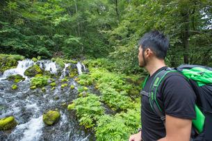 トレッキングで滝を見る青年の素材 [FYI01030330]