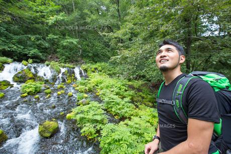 トレッキングで滝を見る青年の素材 [FYI01030341]