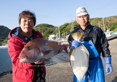 漁港で魚を持つ女将と船長の素材 [FYI01030563]