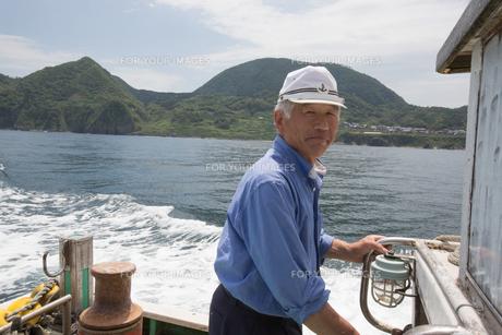 漁船を操縦する船長の素材 [FYI01030564]