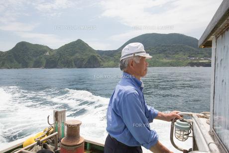 漁船を操縦する船長の素材 [FYI01030576]