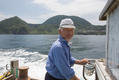 漁船を操縦する船長の素材 [FYI01030628]