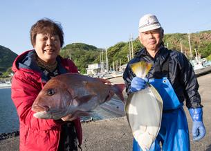 漁港で魚を持つ女将と船長の素材 [FYI01030688]
