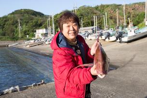 漁港で魚を持つ女将の素材 [FYI01030862]