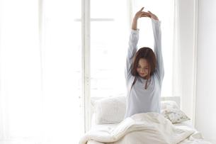 ベッドで伸びをする女性の素材 [FYI01032232]