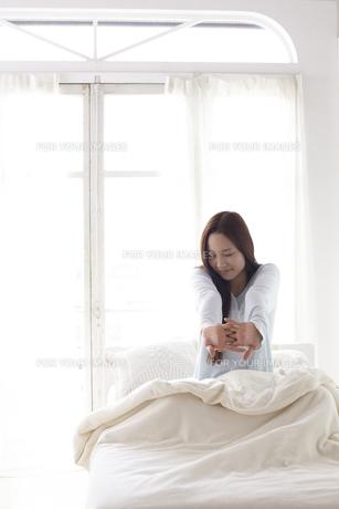 ベッドで伸びをする女性の素材 [FYI01032242]