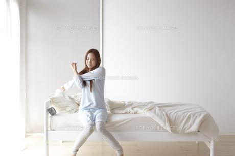 ベッドに座り伸びをする女性の素材 [FYI01032265]