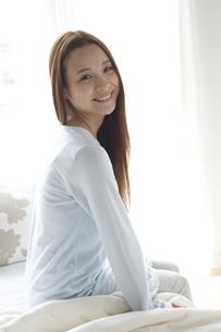 ベッドに座る女性の素材 [FYI01032282]