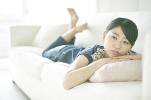 ソファーに寝転びながら何か思いふけっている女性の素材 [FYI01033173]