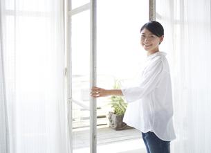窓を開けながら振り返る女性の素材 [FYI01033190]