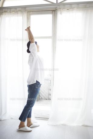 窓際でストレッチしている女性の素材 [FYI01033192]