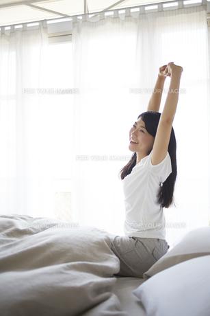ベッドの上でストレッチをする女性の素材 [FYI01033204]