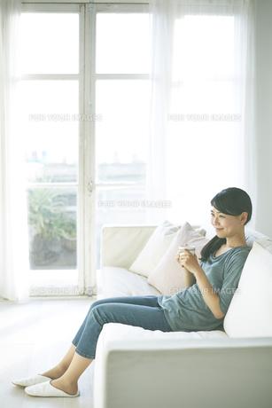 ソファーの上で飲み物を飲んでいる女性の素材 [FYI01033232]