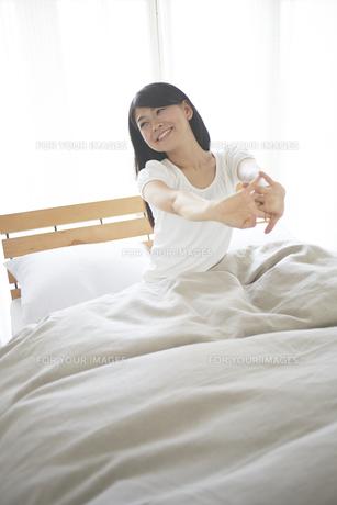 ベッドの上でストレッチをする女性の素材 [FYI01033241]