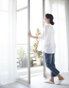窓を開ける女性の素材 [FYI01033251]