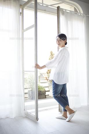 窓を開けながら振り返る女性の素材 [FYI01033255]