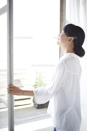 窓を開ける女性の素材 [FYI01033259]