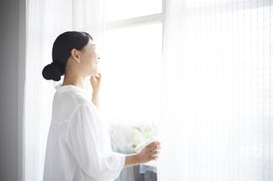 窓の外を眺める女性の素材 [FYI01033282]