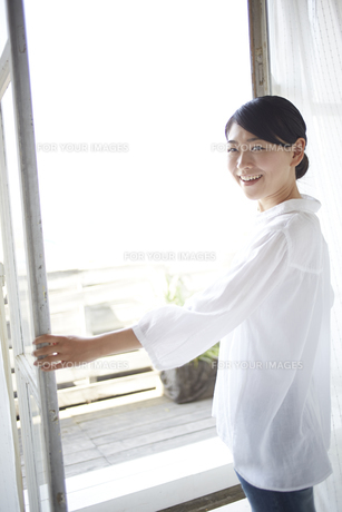 窓を開けながら振り返る女性の素材 [FYI01033299]