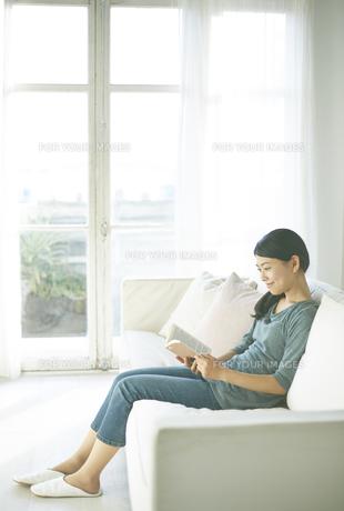 ソファーの上で読書している女性の素材 [FYI01033318]