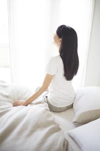 ベッドの上でストレッチをする女性の素材 [FYI01033321]