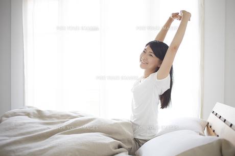 ベッドの上でストレッチをする女性の素材 [FYI01033326]