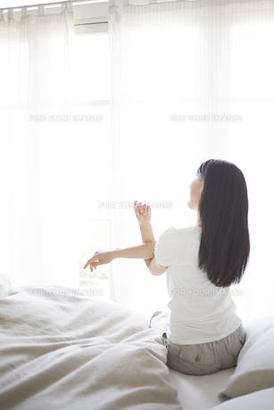 ベッドの上でストレッチをする女性の素材 [FYI01033331]