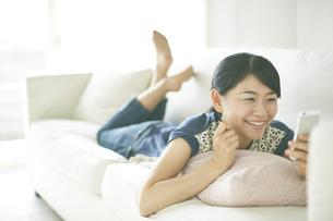 ソファーの上で携帯を見ながら楽しそうな顔をしている女性の素材 [FYI01033332]