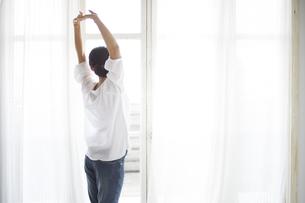 窓際でストレッチしている女性の素材 [FYI01033348]