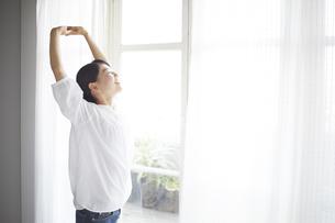 窓際でストレッチしている女性の素材 [FYI01033354]