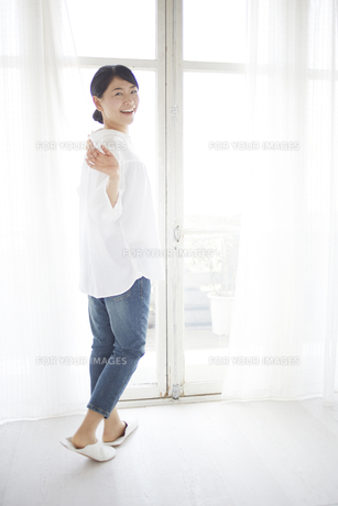 窓際で部屋の中の人に手をふる女性の素材 [FYI01033361]